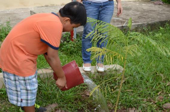A boy, whose mom works in JnJ, happily waters the plant he has planted himself
